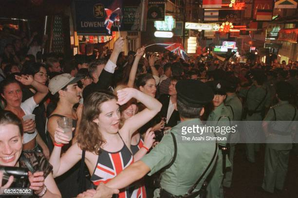 People celebrate after the Handover ceremony at Lan Kwai Fong area on July 1 1997 in Hong Kong