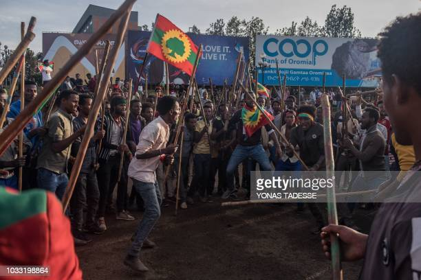 People celebrate as they hold up the Oromo flag ahead of the return of a formerly banned antigovernment group the Oromo Liberation Front in the...