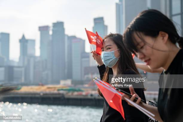 People celebrate as they wave Hong Kong flags and China national flags during a flag raising ceremony as part of China's National Day celebrations on...