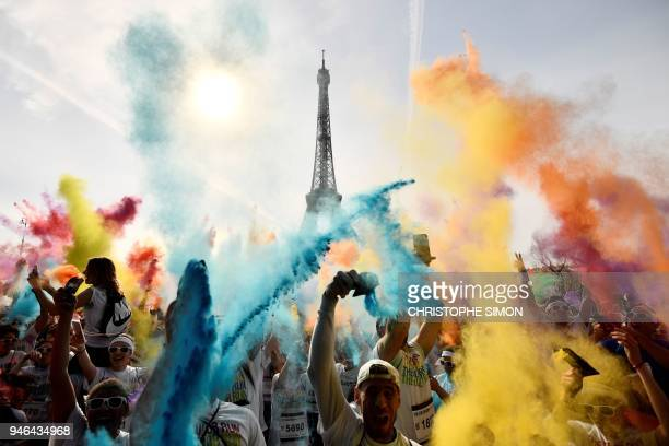 TOPSHOT People celebrate at the end of the Color Run 2018 race in front of the Eiffel Tower in Paris on April 15 2018 The Color Run is a five...