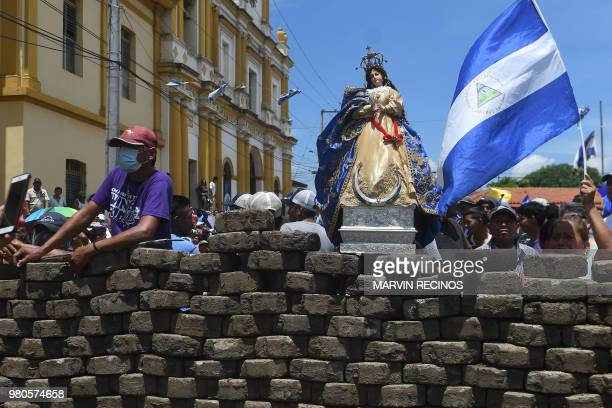TOPSHOT People celebrate behind a barricade after the arrival of bishops of the Episcopal Conference and members of the Civic Alliance in Masaya...