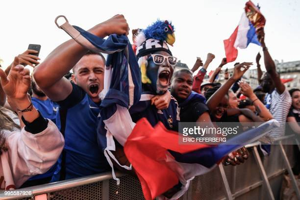 TOPSHOT People celebrate France's first goal as they gather at a fan zone in Paris on July 10 2018 to watch the Russia 2018 World Cup semifinal...