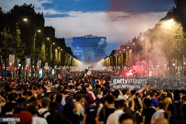 TOPSHOT People celebrate France's victory in the Russia 2018 World Cup final football match between France and Croatia on the ChampsElysees avenue in...