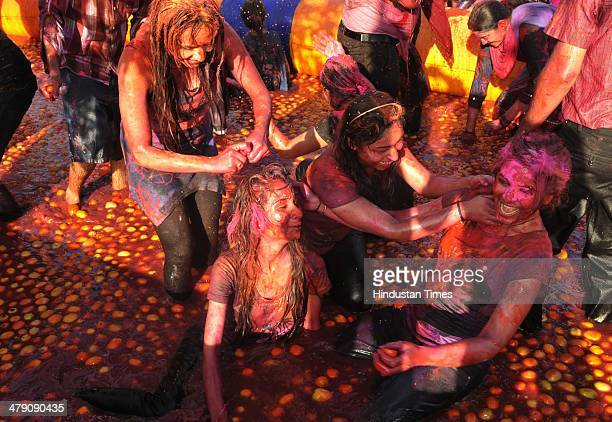 People celebrate Holi festival with tomatoes on March 16 2014 in Indore India The festival falls on the last full moon day of Falgun according to...