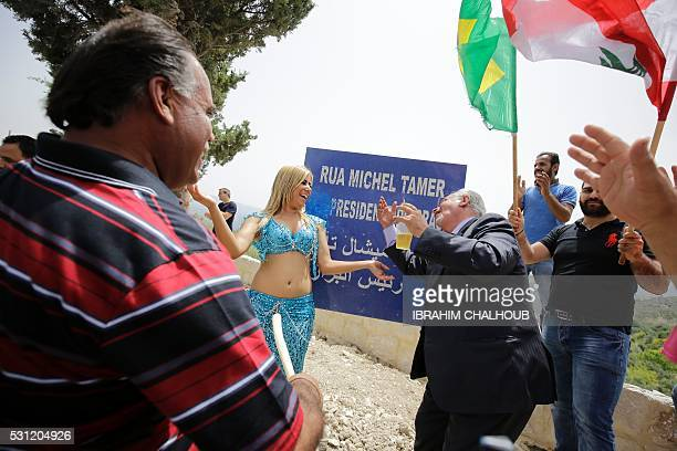 People celebrate in front of a plaque reading in Portuguese and Arabic Street Michel Temer Vice President of Brasil after Brazilian of Lebanese...