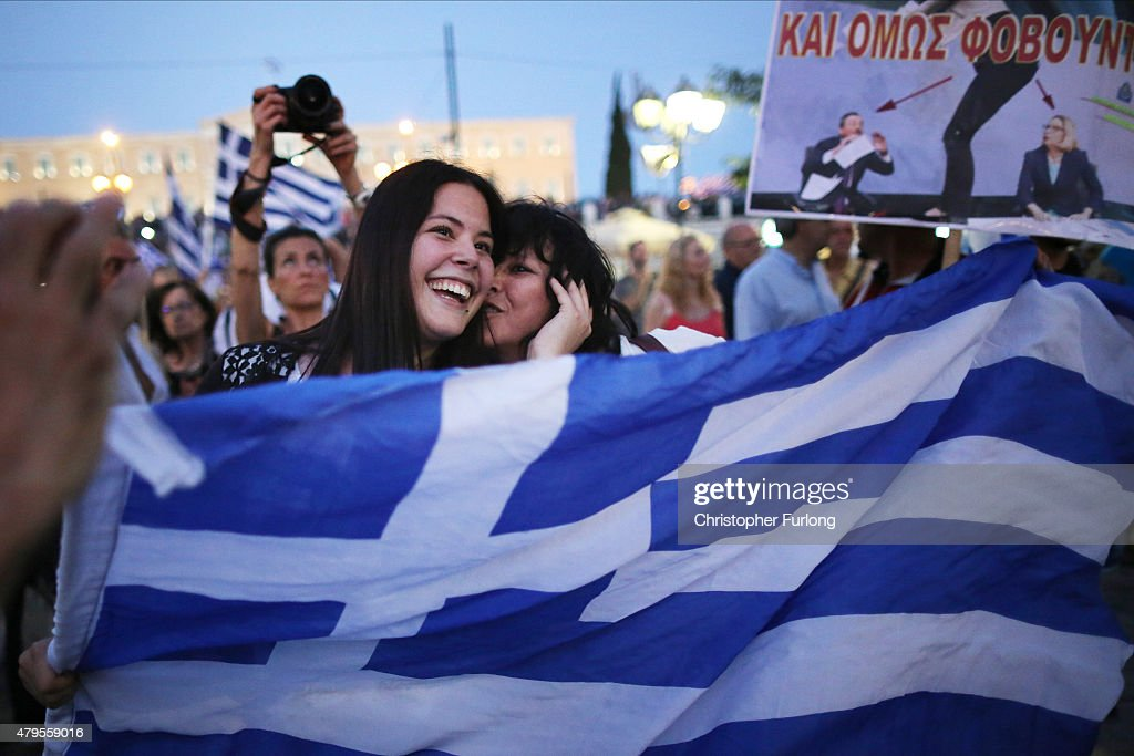 People celebrate in front of the Greek parliament as early opinion polls predict a win for the Oxi, or No, campaign in the Greek austerity referendum. Crowds are begining to gather in the squares of Athens waiting for the official result on July 5, 2015 in Athens, Greece. The people of Greece went to the polls to decide if the country should accept the terms and conditions of a bailout with its creditors. Greek Prime Minister Alexis Tsipras is urging people to vote 'a proud no' to European creditors' proposals, and 'live with dignity in Europe'. 'Yes' campaigners believe that a no vote would mean financial ruin for Greece and the loss of the Euro currency.