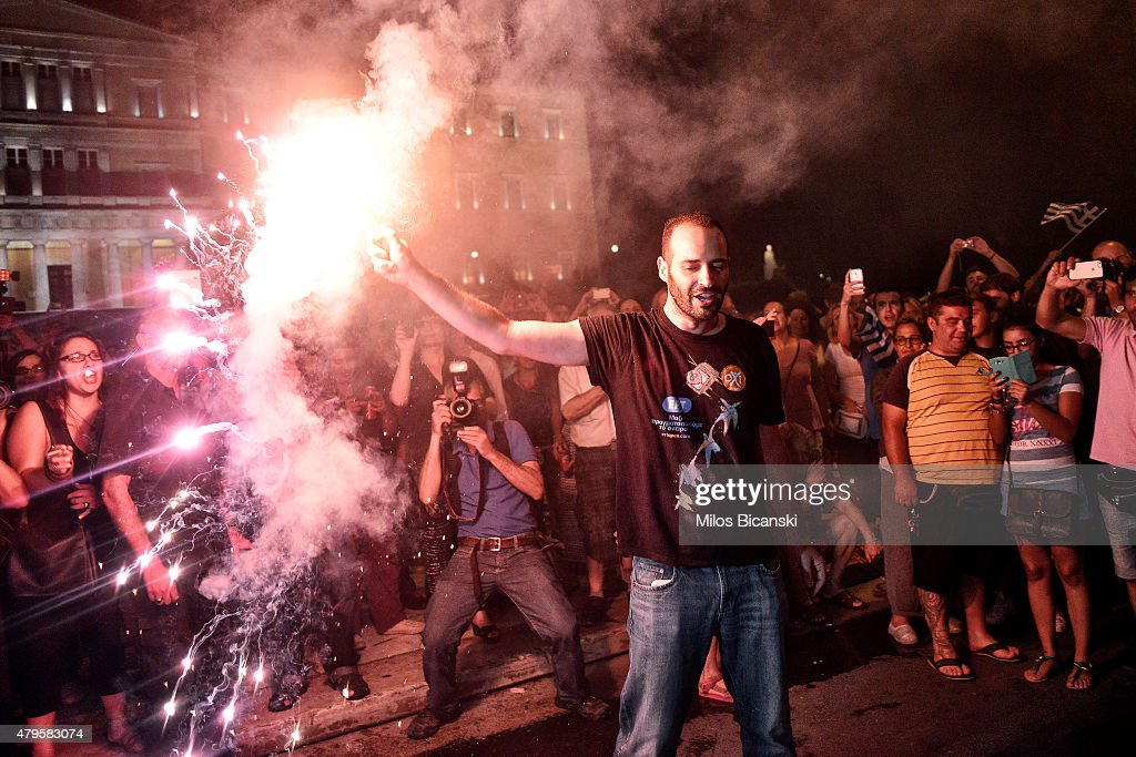 People celebrate in front of the Greek parliament as Greek voters are expected to vote no in the Greek austerity referendum, on July 5, 2015 in Athens, Greece. The people of Greece are going to the polls to decide if the country should accept the terms and conditions of a bailout with its creditors. Greek Prime Minister Alexis Tsipras is urging people to vote 'a proud no' to European creditors' proposals, and 'live with dignity in Europe'. 'Yes' campaigners believe that a no vote would mean financial ruin for Greece and the loss of the Euro currency.