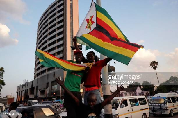 TOPSHOT People celebrate in the streets after the resignation of Zimbabwe's president Robert Mugabe on November 21 2017 in Harare Car horns blared...