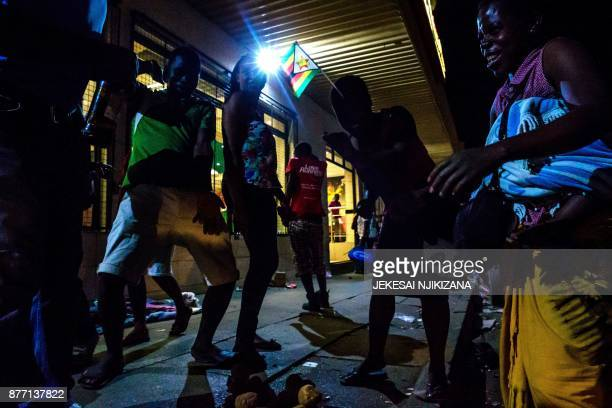 People celebrate in the streets after the resignation of Zimbabwe's president Robert Mugabe on November 21 2017 in Harare Car horns blared and...