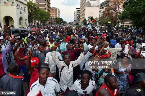 People celebrate in the streets of Harare after the resignation of Zimbabwe's president Robert Mugabe on November 21 2017 The bombshell announcement...
