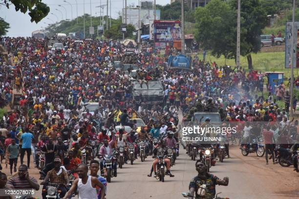 People celebrate in the streets with members of Guinea's armed forces after the arrest of Guinea's president, Alpha Conde, in a coup d'etat in...