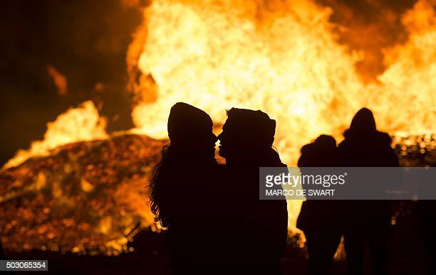 People celebrate New Year's eve in front of a bonfireon a beach in Scheveningen / AFP / ANP / marco de swart / Netherlands OUT