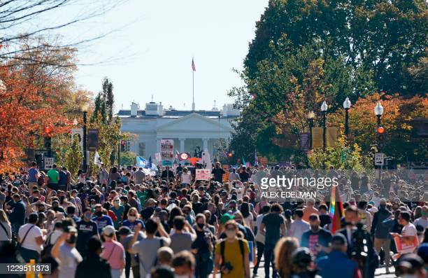 People celebrate on Black Lives Matter plaza across from the White House in Washington, DC on November 7 after Joe Biden was declared the winner of...