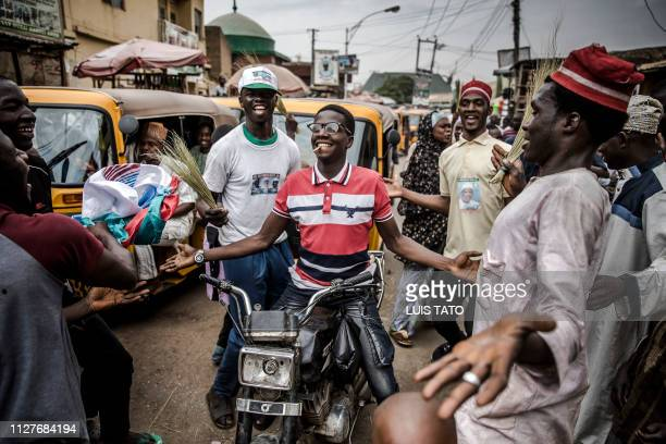 People celebrate on February 27 2019 in a street of Kano the reelection of Muhammadu Buhari as Nigerian president after a delayed poll that angered...