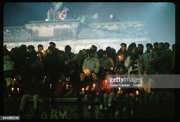 People celebrate sing and carry candles on New Year's Eve at the Brandenburg Gate section of the Berlin Wall just after the fall of communism in East...