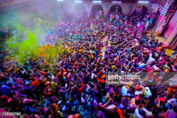 People celebrate the Holi festival and receive green color powder at the Banke Bihari Temple on March 20 2019 in Vrindavam India
