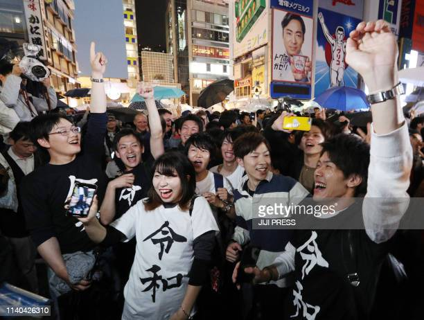 People celebrate the new era of Reiwa on the street of central Osaka on early May 1 2019 Japan's new Emperor Naruhito formally ascended the...