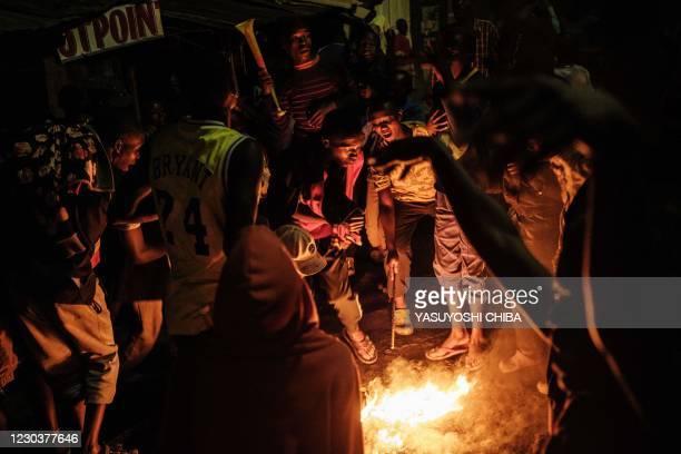 People celebrate the new year dancing around a bonfire in the street of Nairobi's Kibera slum on January 1, 2021.