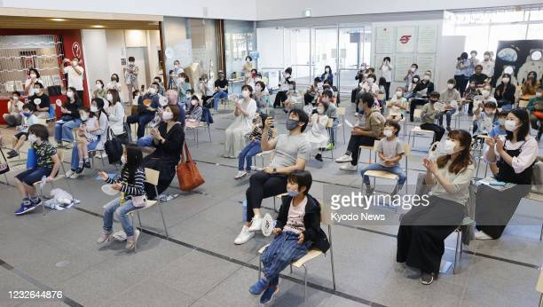 People celebrate the return of Japanese astronaut Soichi Noguchi to Earth on May 2 in front of a monitor screen set up at the city hall of Chigasaki,...