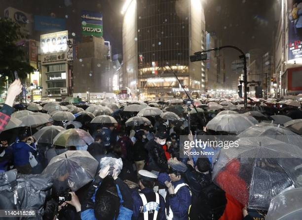 People celebrate the start of Reiwa Japan's new imperial era at a crosswalk in Tokyo's Shibuya district shortly after the clock ticked over to 1200...