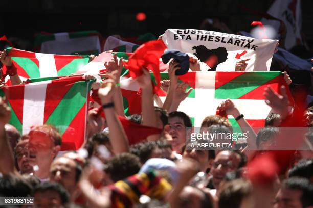 People celebrate while brandishing Basque flags and a banner of the armed Basque separatist group ETA 06 July 2007 during the Chupinazo the beginning...