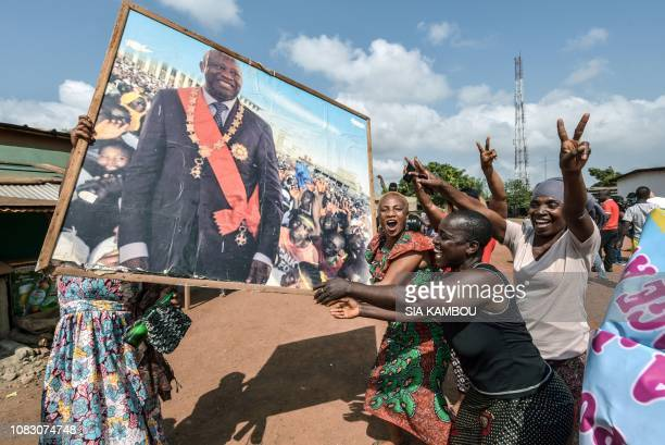 TOPSHOT People celebrate with a portrait of former Ivory Coast president Laurent Gbagbo on January 15 2019 in his birthtown Gagnoa after the news...
