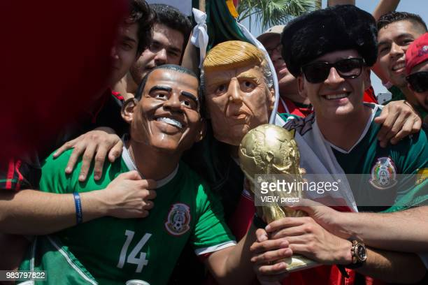 People celebrate with men masked as Former president Obama and President Trump after winning their FIFA World Cup Group F South Korea vs Mexico match...