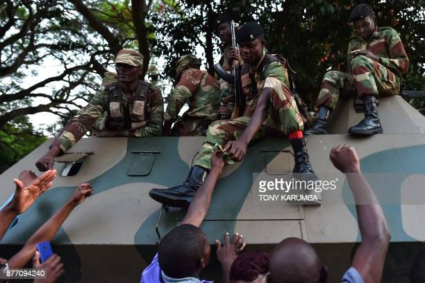 TOPSHOT People celebrate with Zimbabwe Defence Force soldiers on a tank in the streets of Harare after the resignation of Zimbabwe's president Robert...