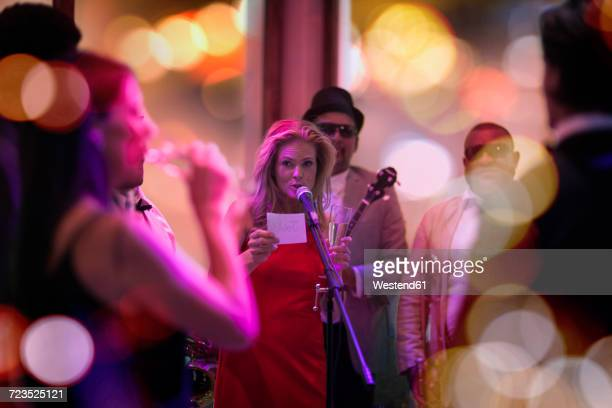 People celebrating and having fun on a party, woman making an announcement
