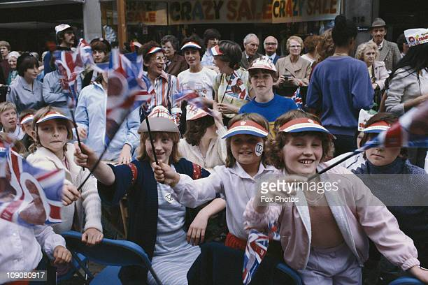 People celebrating and waving flags long the procession route on the day of Prince Charles' wedding to Lady Diana Spencer London 29th July 1981