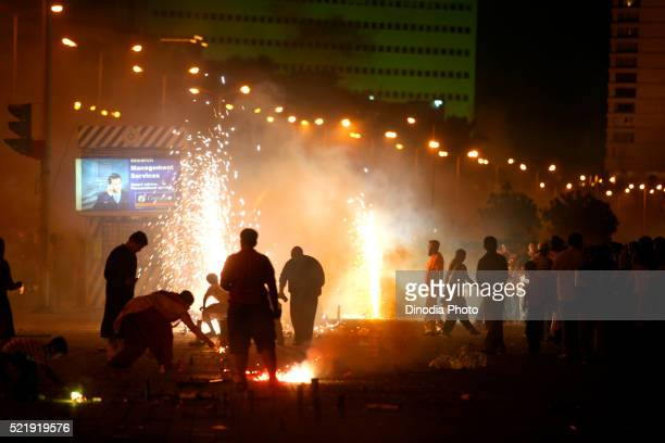 People celebrating Diwali Deepawali, festival-of-lights by bursting fire crackers at Marine-drive in Bombay
