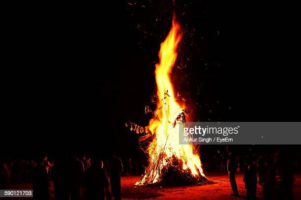people celebrating lohri during night - lohri festival stock pictures, royalty-free photos & images