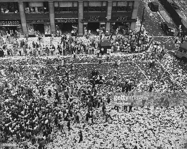 People celebrating on a American street strewn with paper on VJ day.