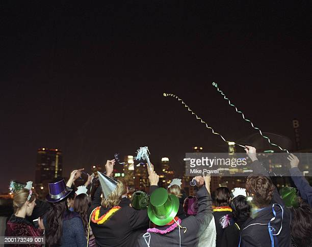 people celebrating on rooftop at new years eve party, rear view - 25 29 years stock pictures, royalty-free photos & images