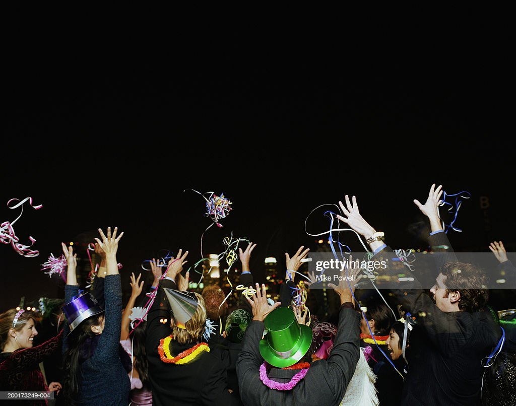 People celebrating on rooftop at New Years Eve party, rear view : Photo