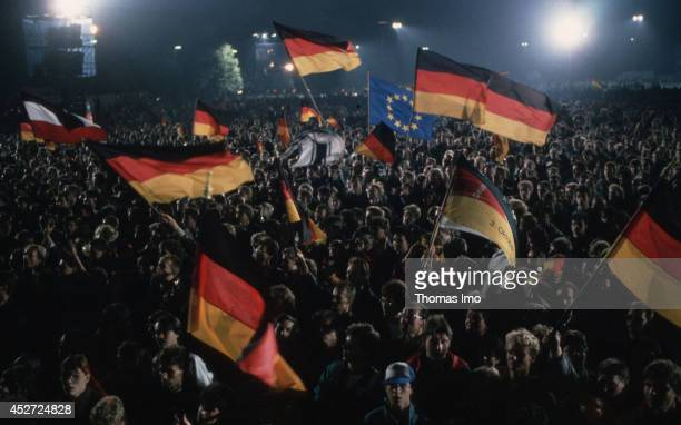 People celebrating the German Unity Day and are waving German Flags on October 03 in Berlin Germany The year 1990 marks the 25th anniversary of the...