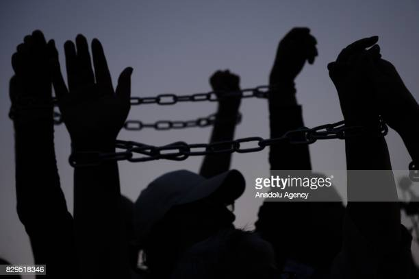 People chain themselves during a protest against the government for using the Smolensk plane crash for political purposes during the monthly...
