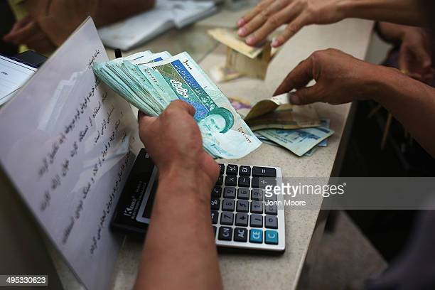 People change foreign currency for Iranian Rials at an exchange shop in the new Isfahan City Center shopping mall on June 2 2014 in Isfahan Iran The...