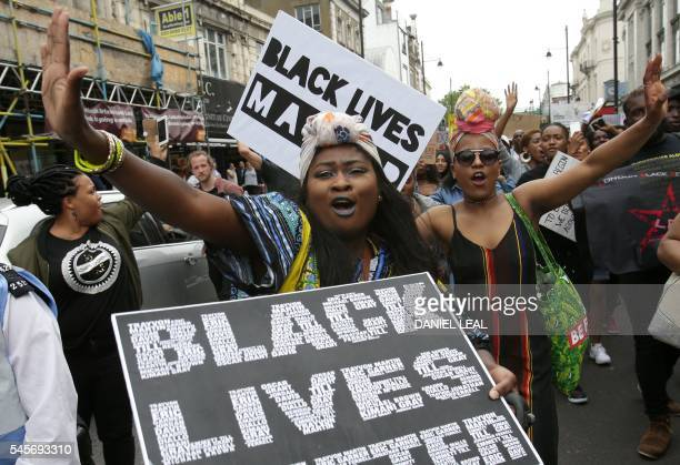 People chant as they march with placards in Brixton south London to protest against police brutality in the US on July 9 after two recent incidents...