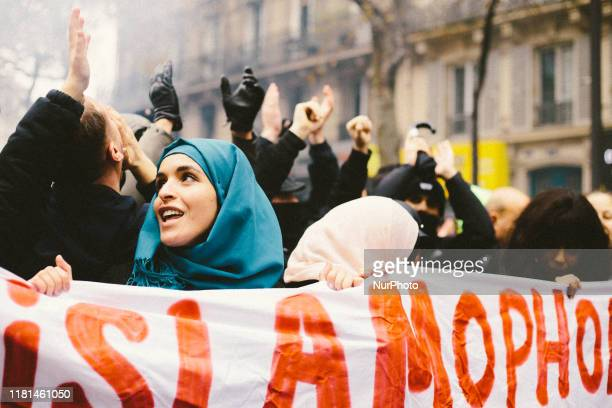People chant slogans and hold placards as they take part in a demonstration march in front of the Gare du Nord, in Paris, on November 10 to protest...