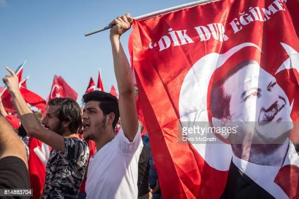 People chant slogans and wave flags as they wait for official ceremonies to begin on the July 15 Martyrs Bridge on the first anniversary of the July...