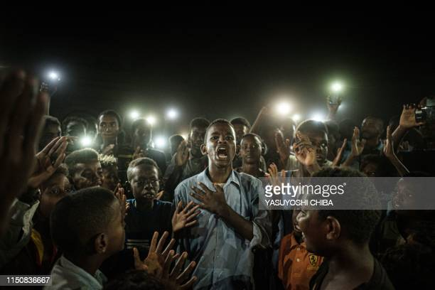 TOPSHOT People chant slogans as a young man recites a poem illuminated by mobile phones before the opposition's direct dialog with people in Khartoum...