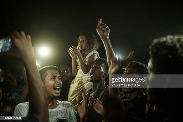 People chant slogans as a young man recites a poem, illuminated by mobile phones, before the opposition's direct dialog with people in Khartoum on...