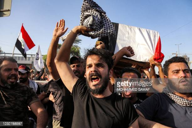 People chant slogans as they march with the body of renowned Iraqi anti-government activist Ihab al-Wazni during a funerary procession in the central...