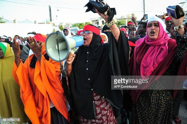 People chant slogans as they protest against the deadly bomb attack in Mogadishu on October 15 after a truck bomb exploded outside of the Safari...