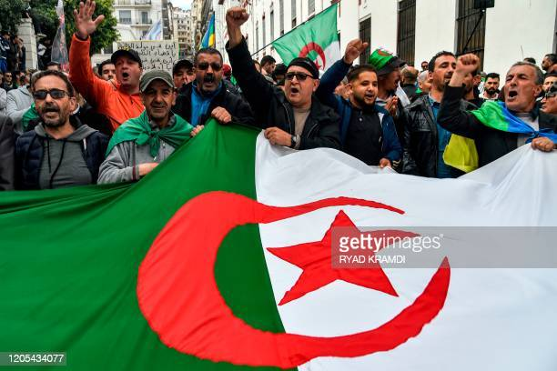 People chant slogans as they wave a large Algerian national flag during a weekly antigovernment demonstration in the capital Algiers on March 6 2020...
