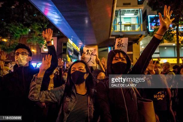 People chant slogans near a police-cordoned-area to show support for a small group of protesters barricaded for over a week inside the Hong Kong...