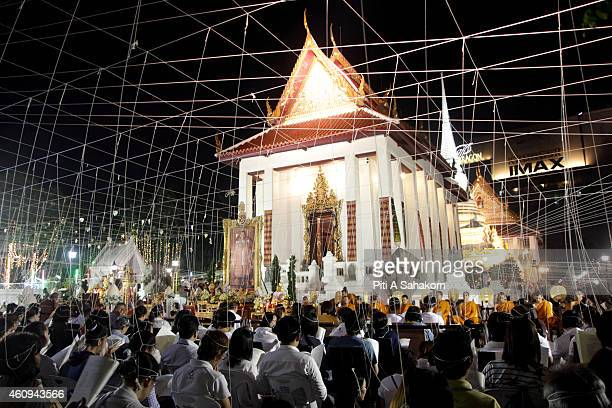 People chanting and offering prayers with Buddhist monks during the New Year's Eve 2015 countdown at Pathum Wanaram Temple in Bangkok