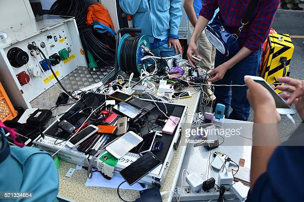 People charge mobile phones at the evacuation center one day after the 2016 Kumamoto Earthquake at the Mashiki Town Hall on April 15 2016 in Mashiki...