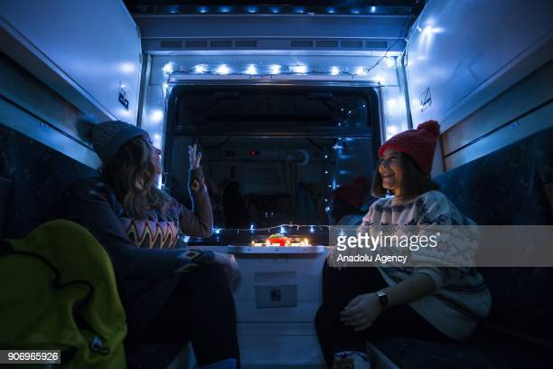 People chat in a illuminated compartment of the Eastern Express which travels from Ankara to Kars in Ankara Turkey on January 12 2018 With the...